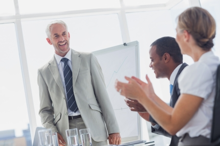 Colleagues applauding smiling manager during a meeting in a meeting room