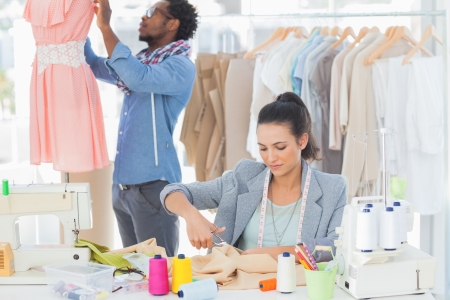 Fashion designer cutting textile at desk while her colleague adjusting dress behind