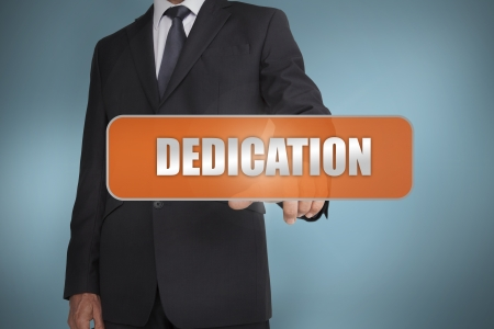 Businessman selecting the word dedication written on orange tag on blue background
