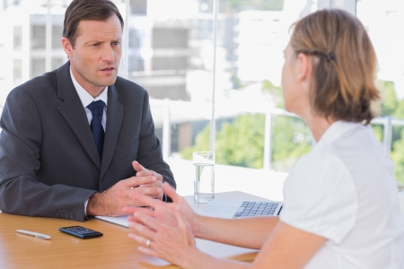 Businessman having a discussion with a job applicant in his office