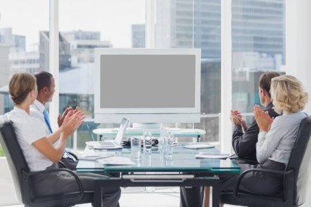 Business people applauding at a screen during a video conference