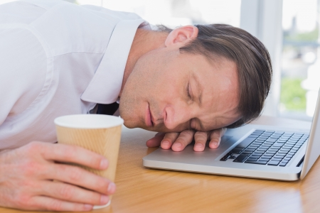 Businessman having a nap on his laptop while he is holding a cup of coffee