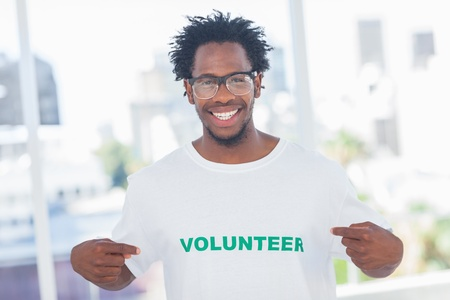 Handsome man pointing to his volunteer tshirt in a modern office