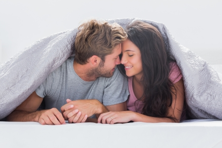 Cheerful couple head against head under the duvet in bedの写真素材