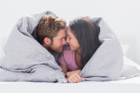 Couple wrapped in the duvet in bed