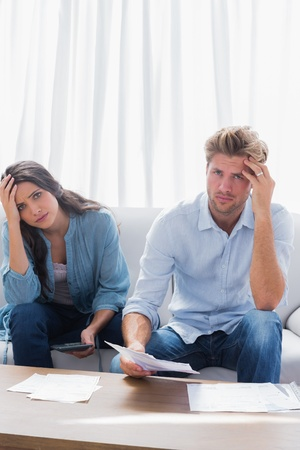 Anxious couple doing their accounts in the living room