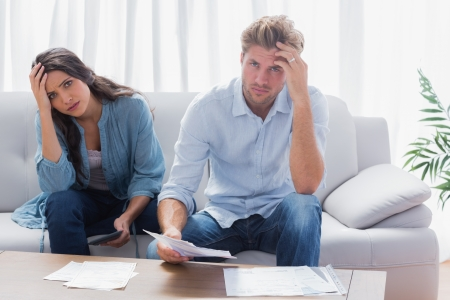 Stressed couple doing their accounts in the living room