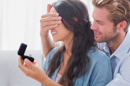 Photo for Man hiding his wifes eyes to offer her an engagement ring for a marriage proposal - Royalty Free Image