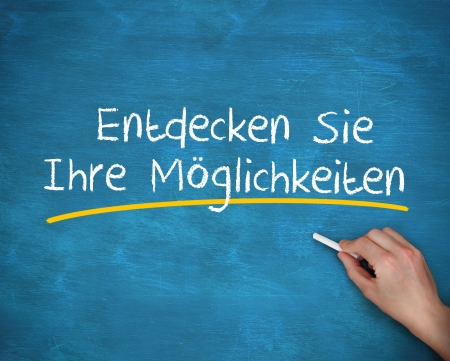 Man writing entdecken sie ihre moglichkeiten with a chalk on blue background