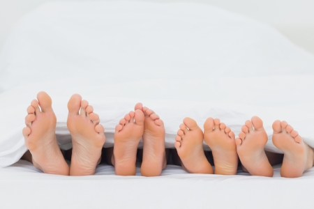 Family on the bed showing their barefoot