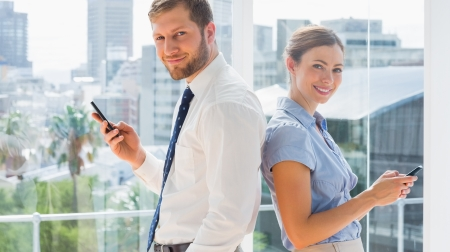 Smiling business team standing back to back and texting in a bright office