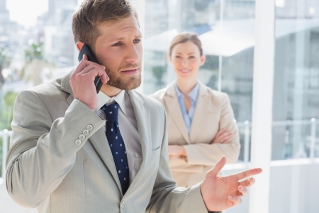 Businessman having phone conversation with colleague standing behind him