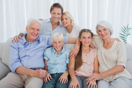 Foto de Extended family sitting on couch and smiling at camera - Imagen libre de derechos