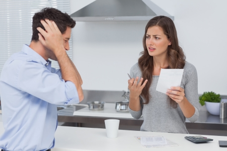 Angry couple doing their accounts in the kitchen