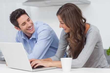 Beautiful couple using a laptop in the kitchen