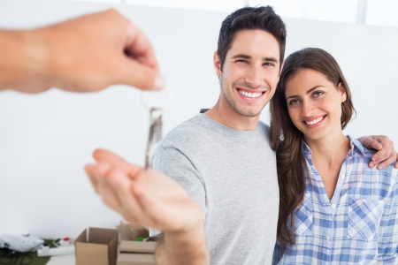 Photo pour Happy man next to his wife being given a house key - image libre de droit