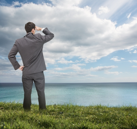 Stylish businessman standing on the grass and looking at the sea