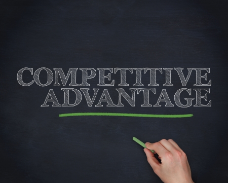 Hand underlining the word competitive advantage in green blackboard