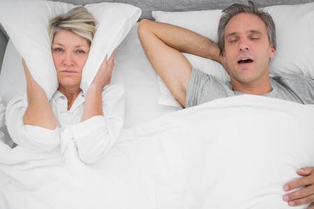 Man snoring loudly as partner blocks her ears at home in bedroom