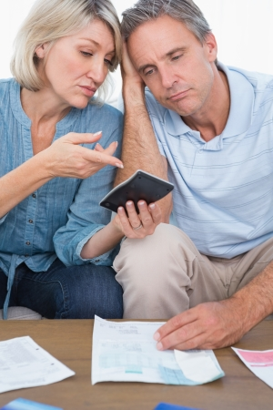 Anxious couple going over their debt at home in living room