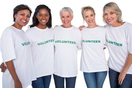 Group of female volunteers smiling at camera on white background