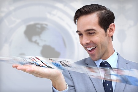 Happy businessman looking at a picture stream on map background
