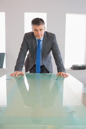 Serious mature businessman standing firmly in front of a desk at office