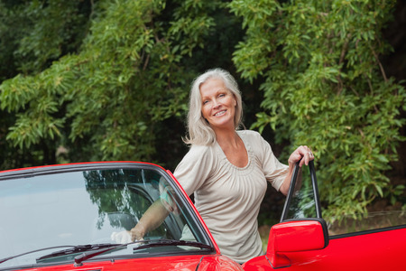 Cheerful mature woman getting off her convertible after long ride