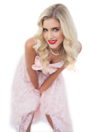 Smiling blonde model in pink dress posing hands on the thighs on white background