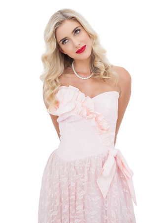Content blonde model in pink dress posing looking away on white background