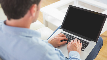 Looking over shoulder of casual man using laptop in bright living room