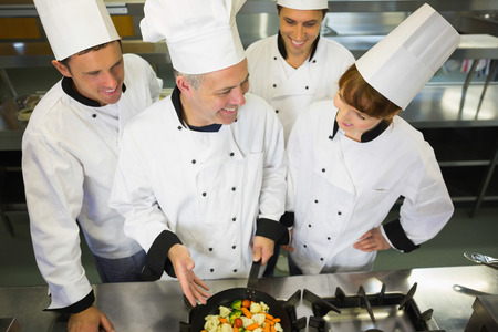 Experienced head chef showing pan to his colleagues in kitchen