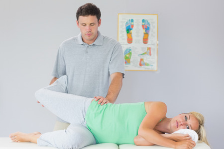 Handsome physiotherapist manipulating patients leg in bright office