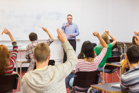 Rear view of students with hands raised with a teacher in the classroom