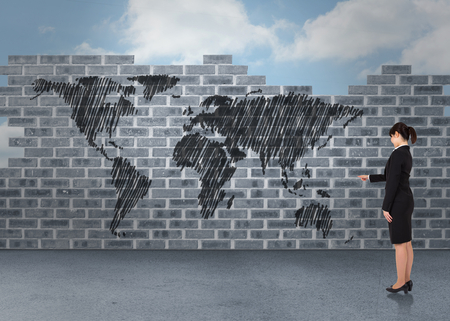 Businesswoman pointing against world map doodle against wall
