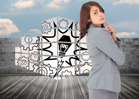 Worried businesswoman against brick lined wall covering half sky