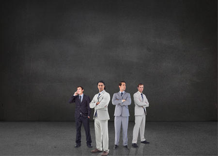 Composite image of attractive businessmen standing arms crossed