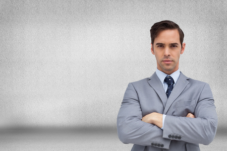 Composite image of young businessman looking at camera