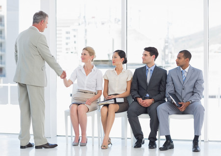 Businessman shaking hands with woman besides people waiting for job interview in a bright office