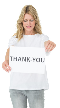 Smiling young female volunteer holding 'thank you' paper over white background