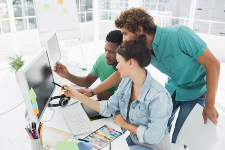 Photo for Side view of three artists working on computer at the office - Royalty Free Image