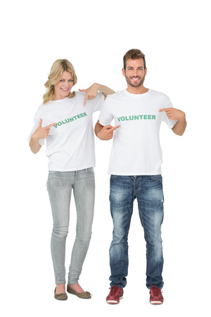 Portrait of two happy volunteers pointing to themselves over white background