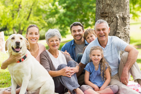 Photo for Portrait of an extended family with their pet dog sitting at the park - Royalty Free Image