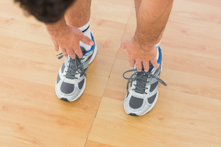 Closeup low section of a sporty man stretching hands to legs in fitness studio