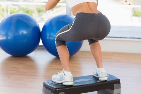 Low section rear view of a fit young woman exercising on step in gym
