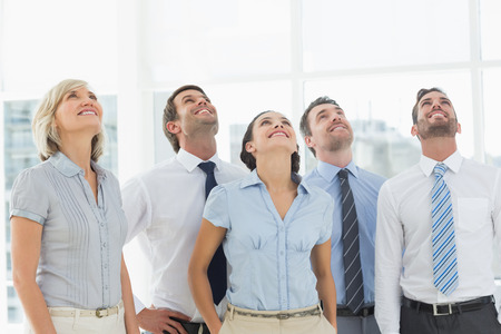 Smiling business team looking up in a bright office