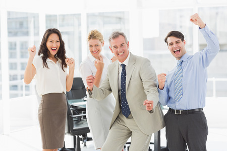 Business team cheering at the camera in the office