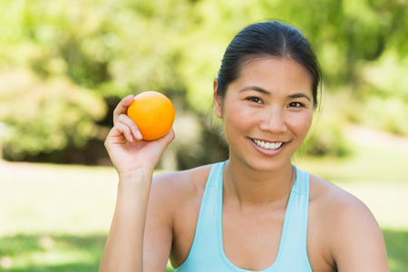 Portrait of a healthy and beautiful young woman holding orange in the park
