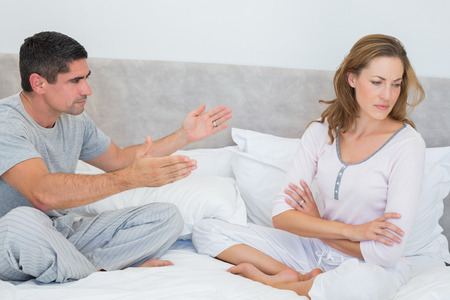 Mid adult couple fighting in bedroom