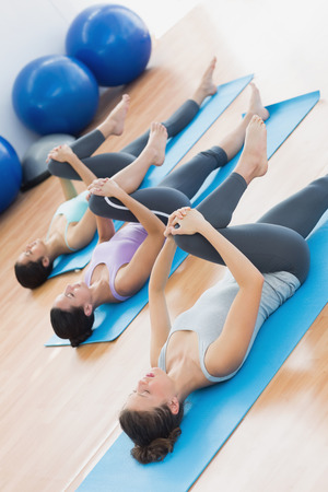 Full length of sporty young people stretching legs in fitness studio